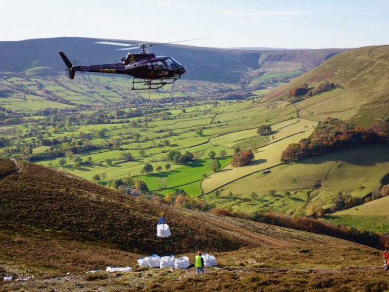 A-helicopter-lowers-stone-on-to-the-Ringing-Roger-path-leading-up-to-Kinder-Scout-in-the-Peak-District-with-Edale-behind.-Work-on-the-path-is-funded-by-Mend-Our-Mountains.-Photo-Adam-Lon